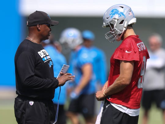 Lions head coach Jim Caldwell talks with quarterback