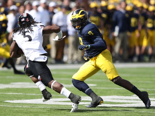 Michigan's Mike McCray pursues Cincinnati's Mike Boone
