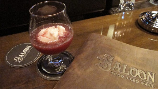 The Saloon, a wood-fired grill that opened Friday in Coconut Point, features a leatherbound cocktail guide. Pictured is The Saloon Punch, a signature drink made with blueberry moonshine, limoncello, muddled fresh blueberries and lemon sorbet.