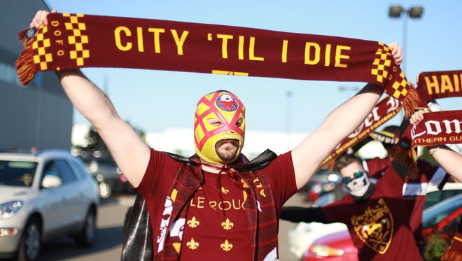 Detroit City FC fan Abe Dorow of Wayne, aka Mustachio, holds up his teams flag for a photo before the start of the match against Michigan Bucks on May 13, 2015, at Ultimate Soccer Arenas in Pontiac.