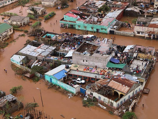 Residents stand on rooftops in a flooded area of Buzi,