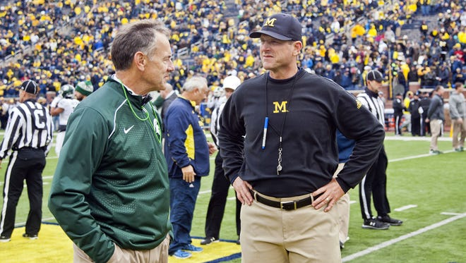 Mark Dantonio, left, and Michigan's Jim Harbaugh appear to stare each other down before last year's game. Dantonio is 7-2 against Michigan, including 1-0 against Harbaugh. The Spartans are 24 1/2-point home underdogs this year against Michigan.
