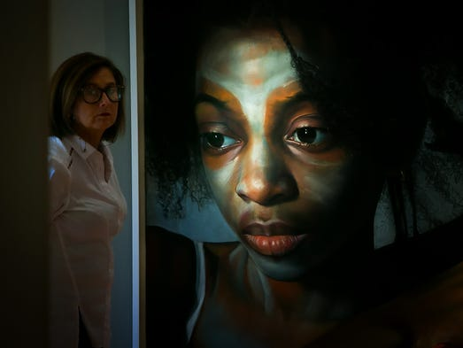 Victoria Manning walks by a painting by artist Margaret