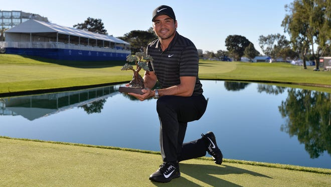 Jason Day poses for a photograph with the winner trophy following the playoff round of the Farmers Insurance Open golf tournament at Torrey Pines Municipal Golf Course - South Co.