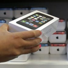 In this file photo, a sales person pulls out an iPhone 5s for a customer.