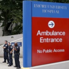 Police officers block an entrance at Emory University Hospital after the arrival of an ambulance transporting former Ebola patient Dr. Kent Brantly, in Atlanta on Aug. 2, 2014.