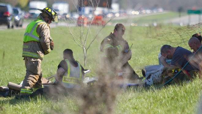 Emergency personnel rest on the scene of a double-fatal accident on southbound U.S. 23 which occurred Sunday, April 23, 2017.