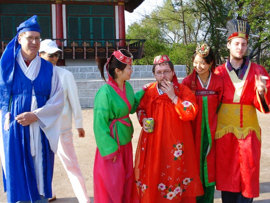 In this photo taken May 30, 2009 and released by Christopher Barbara, Gareth Johnson, centre,  smokes with other foreign tourists on a Young Pioneer Tours as they wear traditional costumes during a visit to the Pyongyang Film Studio in Pyongyang in North Korea. British expatriate Gareth Johnson founded the Young Pioneer Tours agency in 2008 and has built up a business attracting young travelers with a competitively priced catalog of exotic-sounding, hard-partying adventures into the world's most isolated country. (Christopher Barbara via AP)