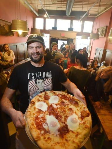Dave Mancini holding an extra large Bismarck pizza