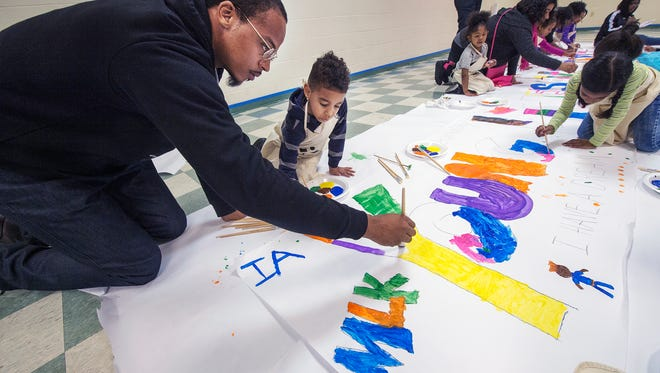 Richard Craighead, left, of York, helps his son Richard Jr. paint a 'Young Lives Matter' poster during the annual MLK Day of Service and breakfast at Crispus Attucks in York on Monday.