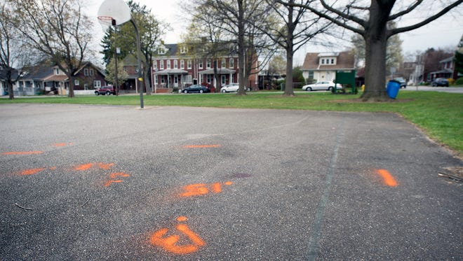 Spray-paint marks the area where one man was killed and two others were injured Sunday evening at Girard Park near the 600 block of East Maple Street.