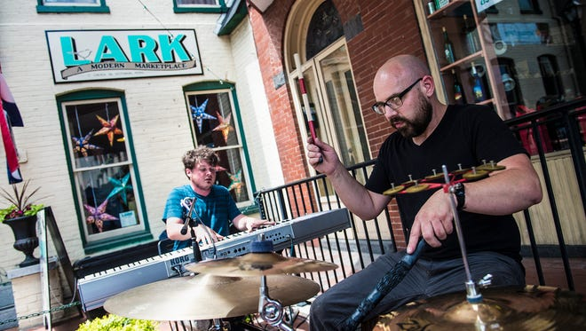 Buskers Ethan Larsh, left, and Brian Forberger, right, play outside of gallery and retail store Lark in Gettysburg on May 29, 2016.