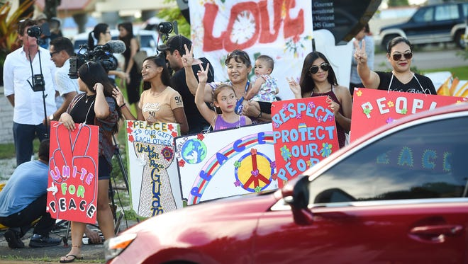 Guam residents wave to motorists during a peace rally at the Chief Quipuha Statue in Hagåtña on Aug. 14, 2017.