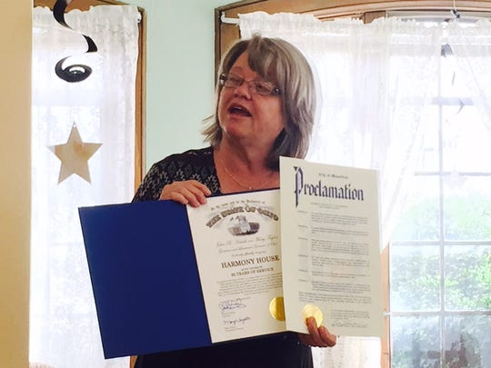 Harmony House director and CEO Vicki Kane displays two proclamations congratulating the homeless shelter on 25 years. One was from the city of Mansfield and the other from the state.