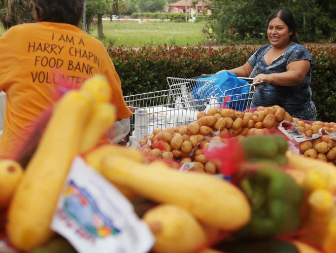 Tranceta Mateo Francisco, of Bonita Springs, smiles as she browses for fresh vegetables at the Harry Chapin Food Bank mobile pantry at St. Leo the Great Catholic Church on Saturday.