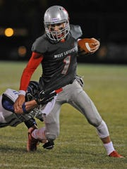 West Side quarterback Mikey Kidwell scrambles for yardage Friday night against Tipton.