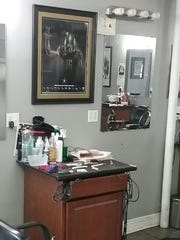 A framed mural of Vanderbilt freshman wide receiver Kalija Lipscomb hangs at the work station of his father, Karanja Lipscomb, at The Avenue Barber Shop in New Orleans.