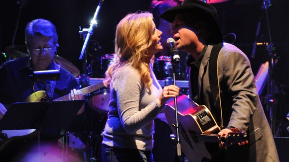 "Garth Brooks and Trisha Yearwood perform ""Take Me"" at the George Jones Tribute - Playin' Possum: The Final No Show, on Friday, Nov. 22, 2013, at the Bridgestone Arena in Nashville, Tenn. (Photo by Frank Micelotta/Invision/AP)"