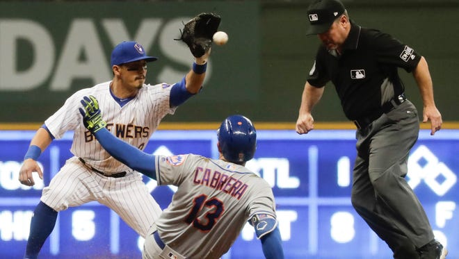 Milwaukee Brewers' Tyler Saladino takes the throw as New York Mets' Asdrubal Cabrera is out at second trying to stretch a single into a double during the 10th inning of a baseball game Friday, May 25, 2018, in Milwaukee.