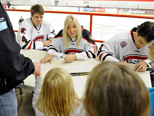 St. Cloud State hockey team members Ben Storm (left to right), Caroline Markstrom and Andrew Prochno talk with young fans and sign autographs at the Moose Sherritt Arena Tuesday in Monticello.