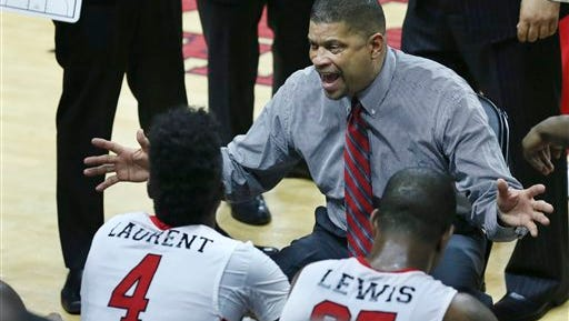 Rutgers head coach Eddie Jordan, seated center, instructs his players vs. Minnesota.