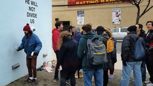 "Actor Shia LeBeouf, left, stands in front of a live-steam camera with the words ""HE WILL NOT DIVIDE US"" posted on a wall outside of the the Museum of the Moving Image as members of the public join LeBeouf in chanting the words ""He will Not Divide Us"" in the Queens borough of New York. LaBeouf has spent the first four days of the Trump presidency swaying, dancing and chanting, along with anyone who wants to join in. The project by LeBeouf and two other artists opened on Jan. 20 and is expected to go for 4 years, or for ""the duration of the presidency."""