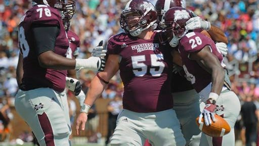 Maroon's Damien Robinson (78) and Dylan Holley (55) celebrate with running back Derrick Milton (28) following his second-half touchdown during Mississippi State's spring NCAA college football game Saturday, April 20, 2013, in Starkville, Miss. (AP Photo/Austin McAfee)