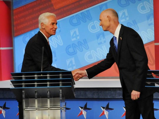 Florida Democratic gubernatorial candidate Charlie Crist, left, shakes hands with Gov. Rick Scott during their Oct. 21, 2014, debate in Jacksonville, Fla.