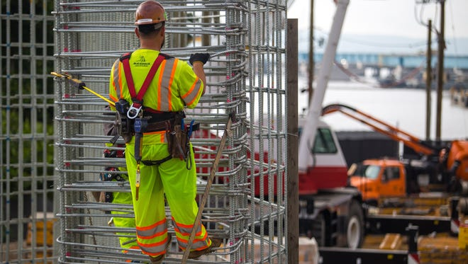 An ironworker ties steel reinforcements for the Rockland abutment of the new Tappan Zee Bridge in July. A flurry of construction activity is taking place along Piermont Avenue in South Nyack and River Road in Upper Grandview.