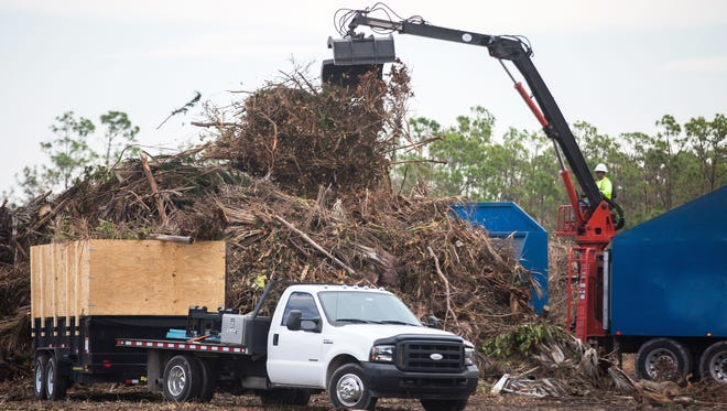 Workers remove debris made by Hurricane Irma from a collection site on Wiggins Pass Road in North Naples on Sept. 27, 2017.