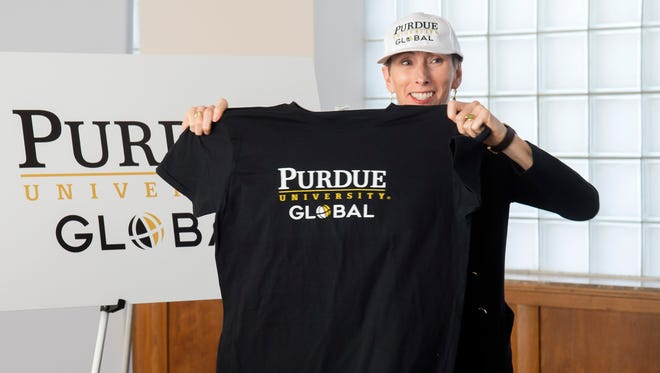 Betty Vandenbosch, chancellor of Purdue Global, shows off shirts and hats from the new online arm of Purdue University, which launched Monday, April 2. Purdue Global is the rebranded Kaplan University, a former for-profit online university now operated by Purdue.