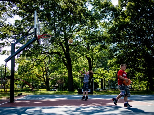 Friends Addison Nichols and Clayton Thompson, both 11, play basketball together Wednesday, July 20, 2016 at Palmer Park in Port Huron.