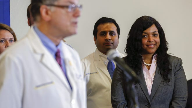 Ebola virus survivor Amber Vinson, right, listens to Dr. Bruce Ribner, medical director of the Serious Communicable Disease Unit at Emory University Hospital during a press conference in Atlanta on Oct. 28.