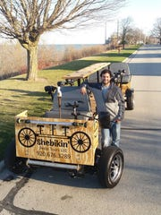 Justin Vannieuwenhoven posing with the pedal pub that