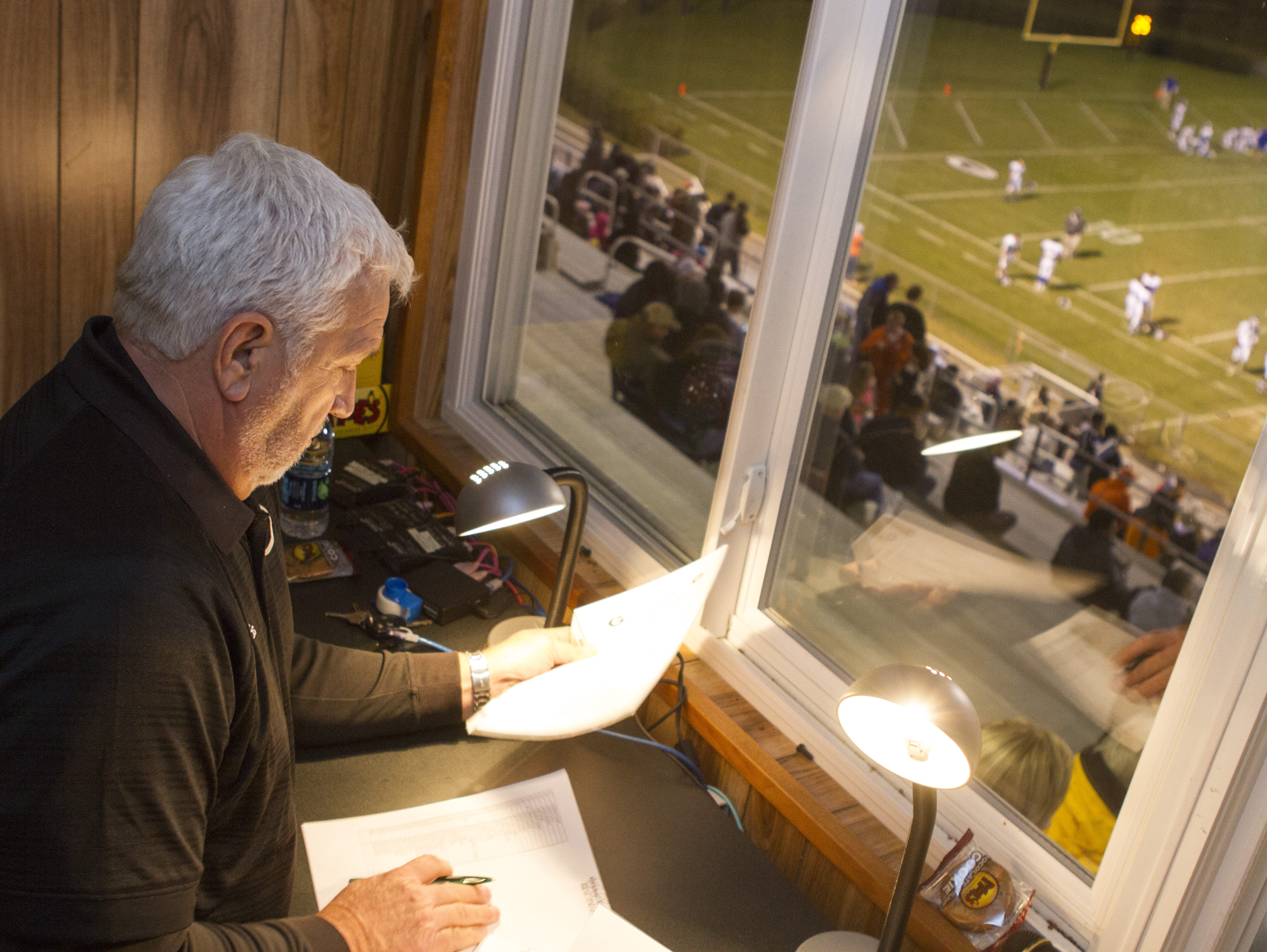 Keith Hannon goes through the starting lineups at Greer High School before the game against Travelers Rest. Hannon is a spotter for his son, Chad, the public address announcer.