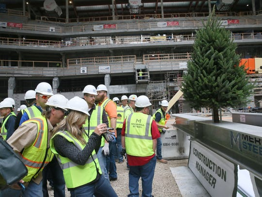 The Milwaukee Bucks hold a topping off ceremony for the new arena.  Guests at the event take photos of the signatures on the beam.