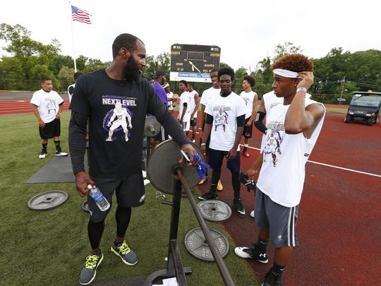 Malcolm Jenkins speaks with participants at his annual free summer football camp in Piscataway.