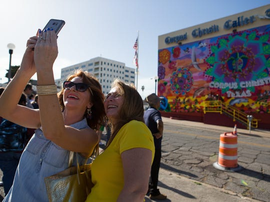 "Lisa Mills and Annette Medlin take a selfie in front of the ""Endless Sunset: The Colors of Our City"" mural on the Caller-Times building following the dedication ceremony on Friday, Aug. 5, 2016."