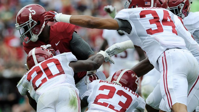 Alabama running back Ronnie Clark (5) is stopped by white team linebacker Shaun Dion Hamilton (20), defensive back Jabriel Washington (23) and linebacker Christian Miller (34)in first half action of the A-Day Spring Game at Bryant-Denny Stadium in Tuscaloosa, Ala. on Saturday April 18, 2015.