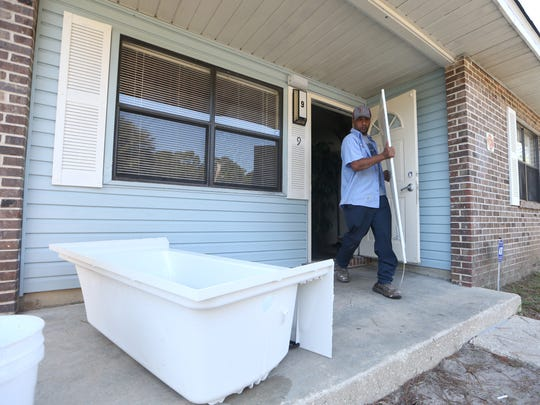 Maintenance workers Jerry Maul removes a bath tub from