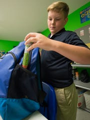 Bruce Macolley, 10, of Dover, places his EpiPen into his backpack during dismissal at St. John's Lutheran School in Dover. The producer of the drug was ordered in August to pay Delaware nearly $900,000.