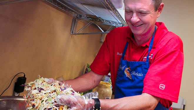 Robert McConnell mixes up a batch of slaw to be served up to visitors to the Lane Ag Center Friday night.  Hundreds filled the center for the 67th Annual Blackman Barbecue.