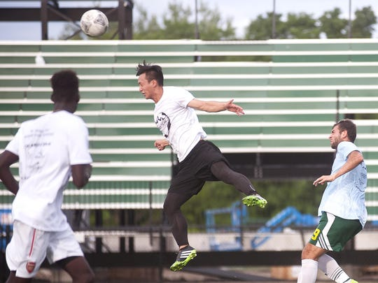 Burlington's Kevin Chu, center, heads a ball clear from danger against South Burlington during the alumni semifinals of the Stefan Pierson Memorial Soccer Tournament at Virtue Field on Saturday.