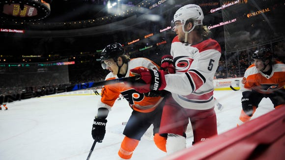 Flyers' Oskar Lindblom (54) collides with Hurricanes' Noah Hanifin (5) Thursday, April 5, 2018 at the Wells Fargo Center in Philadelphia, Pa.