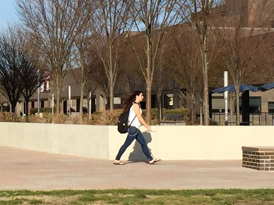 A student makes her way across the SUNY Purchase College campus Monday, April 18, 2016, the morning after a police search for a gunman reported on campus.