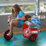 Caleigh Guyer, 8,  peddles her sister Madelyn, 6, who is a patient,  around the play area in the new Golisano Children's Hospital.