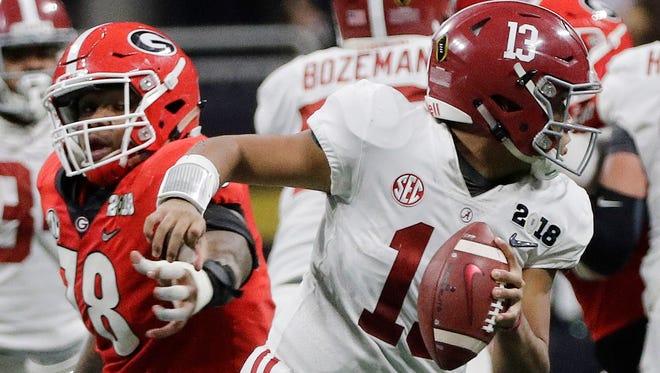 Alabama's Tua Tagovailoa scrambles from Georgia's Trenton Thompson during the second half of the NCAA college football playoff championship game Monday, Jan. 8, 2018, in Atlanta.
