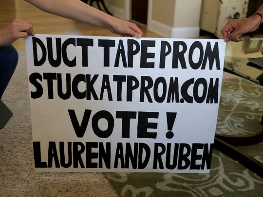 Lauren Gardner and Ruben Taylor made a sign to garner support for a scholarship contest featuring homemade duct tape prom outfits.