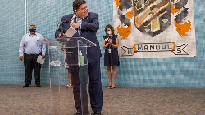 Illinois Governor JB Pritzker sheds his mask after stepping to the podium Monday, July 20, 2020 in the lobby of Manual High School with an introduction by Peoria Public Schools District superintendent Sharon Desmoulin-Kherat. Gov. Pritzker visited the school to highlight the district's summer employment program.