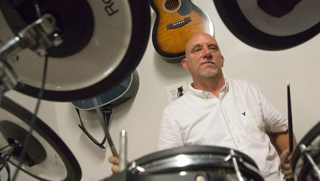 The owner of Second Hand Music, Joseph Smith, plays on a drum set inside his store on 730 Olivesburg Road on Friday. Smith opened the store earlier this year, but will have a grand opening on August 6, when he will have four live bands, food and a guitar giveaway.